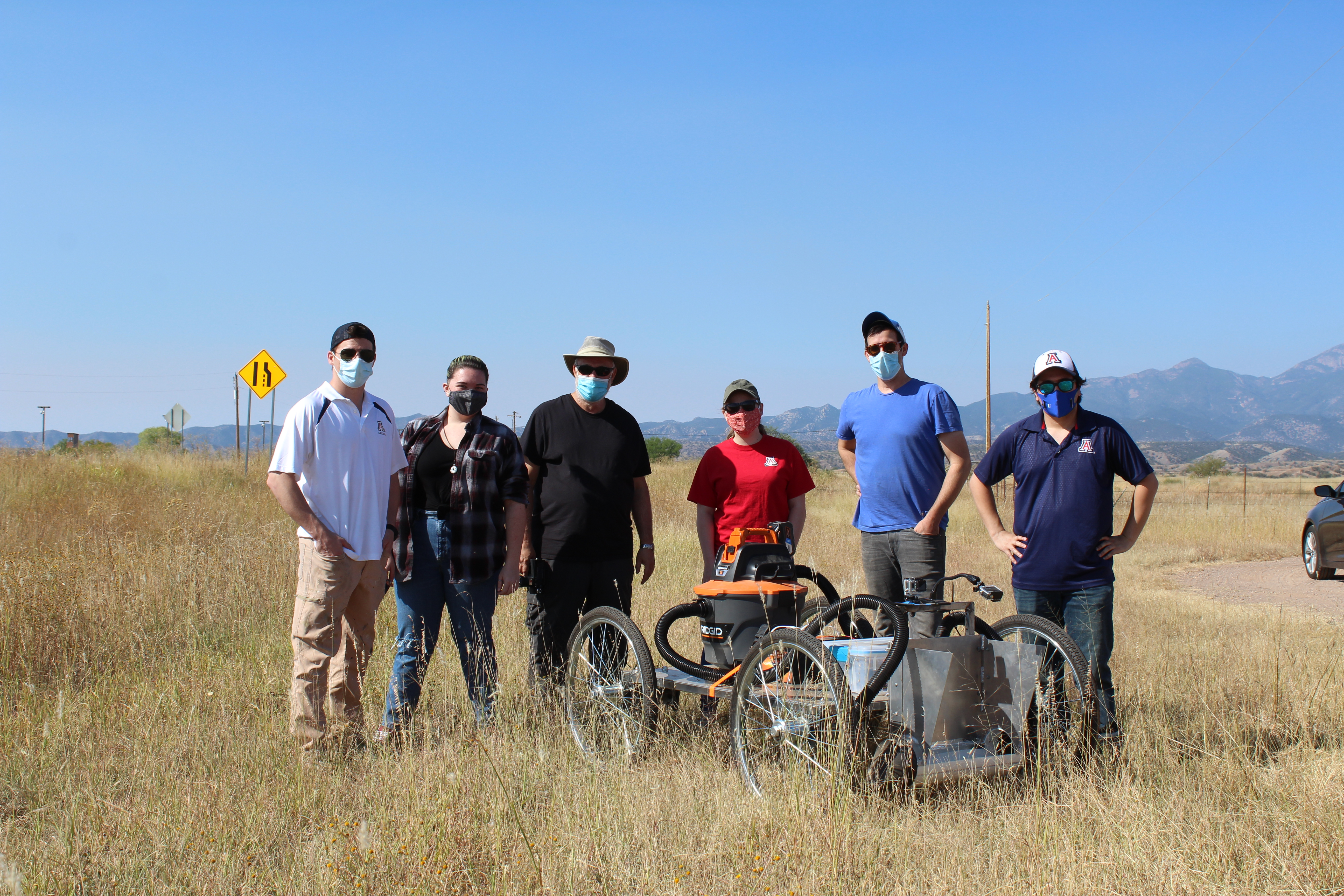 Six people stand in a field around a cart.