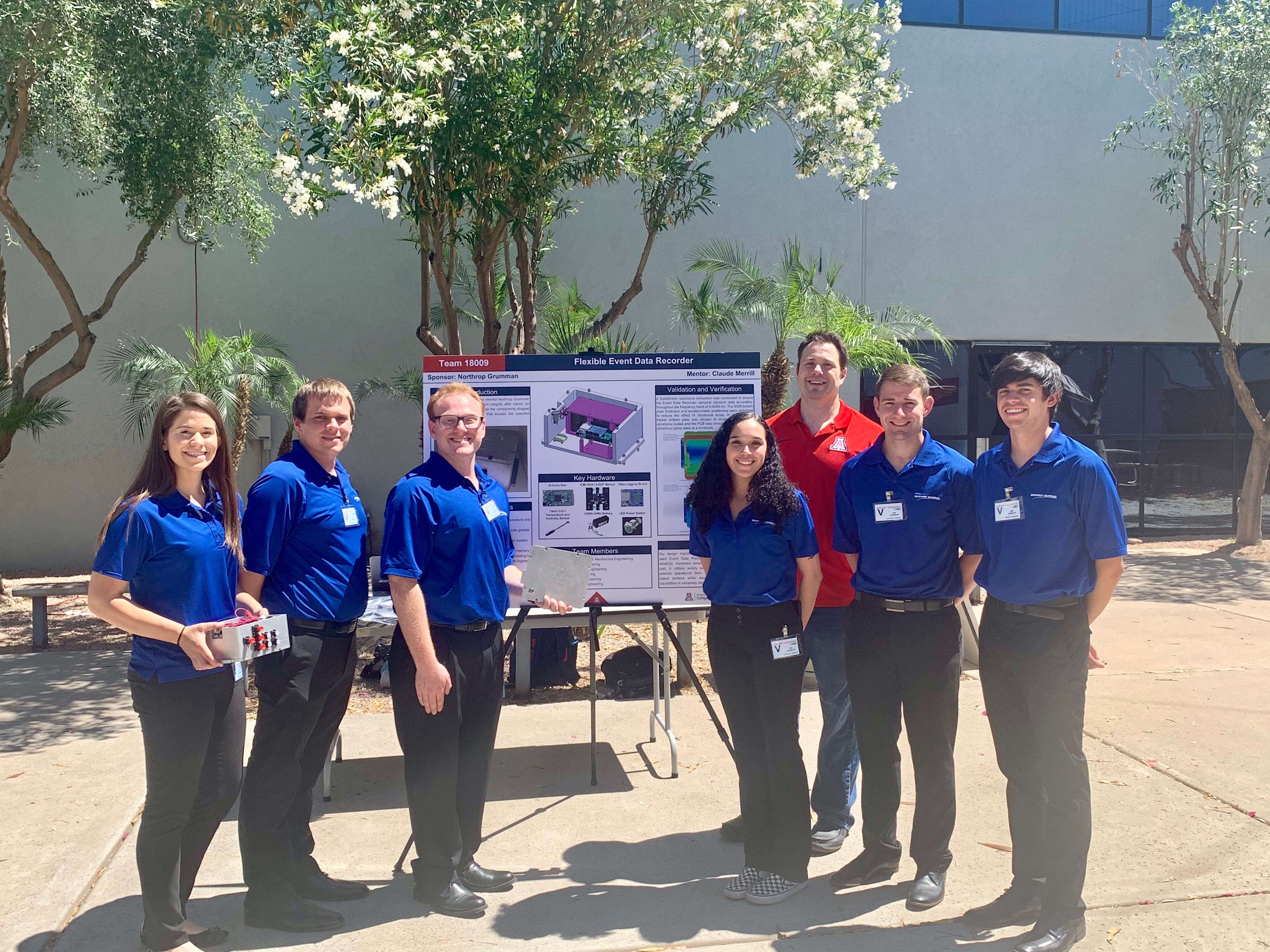 A group of seven people, six in blue polos and one in a red polo) stand next to an academic poster. They are outside and a tree is in the background.