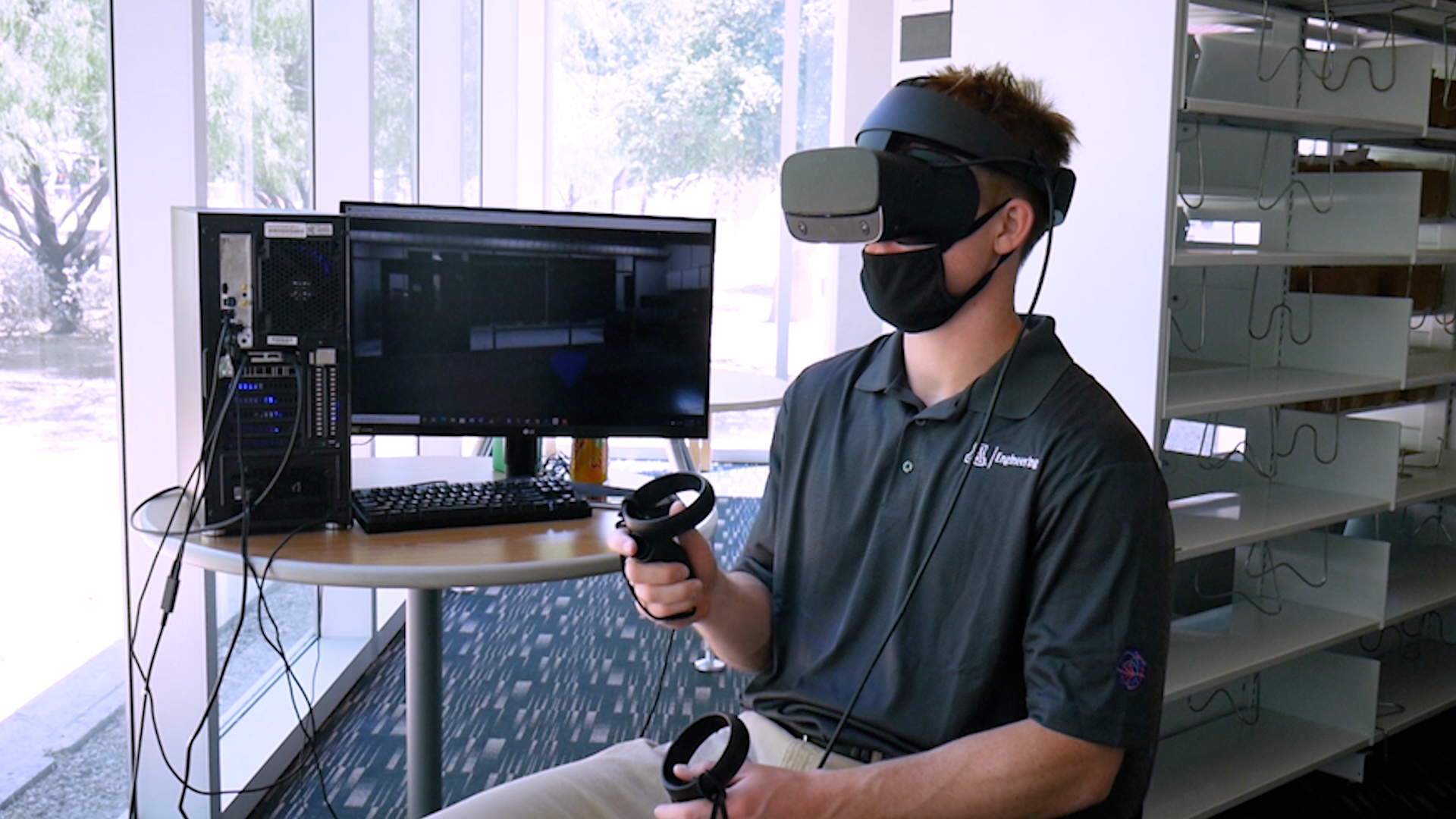 A student wearing a virtual reality headset and sitting next to a computer monitor.