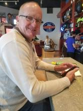 Photo of Claude Merrill sitting at a counter
