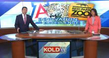 Screenshot of a newscast. Two anchors sit at a news desk. behind them, a photo of a jaguar.