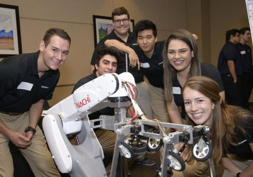 A senior design team stands with their robotics project