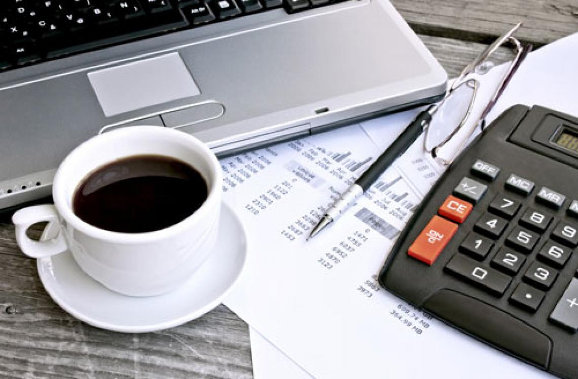 Computer desk with laptop, cup of coffee, and calculator