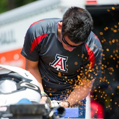 Student wearing UA shirt and protective eyewear uses a circular saw to cut metal, sending up a shower of sparks